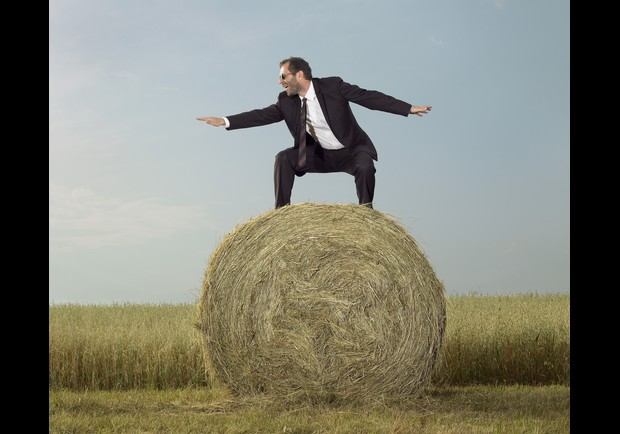 Barefoot businessman striking surfing pose on hay bale
